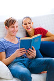 Smiling young couple sitting on sofa with book Stock Photo