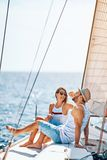 Smiling couple spending time together and relaxing on yacht. Smiling young couple spending time together and relaxing on yacht stock photography