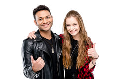 Smiling young couple standing embracing and showing thumbs up Royalty Free Stock Photos