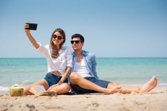 Smiling Young couple taking a selfie on the beach stock photos