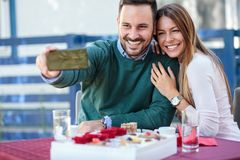 Smiling young couple taking a selfie in an outdoor cafe stock images