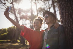 Smiling young couple taking selfie while standing together Stock Photo