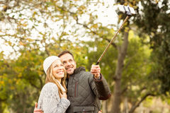 Smiling young couple taking selfies stock images