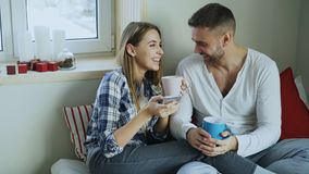 Happy young couple talking and laughing while sitting in on bed and drink coffe in the morning at home. Smiling young couple talking and laughing while sitting Royalty Free Stock Photography