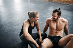 Fit young couple sitting together on a health club floor