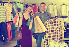 Smiling young couple and teen stands near clothes Royalty Free Stock Images