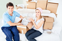 Smiling young couple unpacking boxes with glasses Stock Images