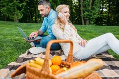 Smiling young couple using smartphone and laptop at picnic. In park royalty free stock photography