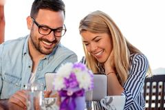 Smiling young couple using a tablet in cafe. Smiling happy young couple browsing internet or looking at pictures on a tablet, drinking coffee in an outdoor cafe royalty free stock image