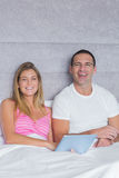 Smiling young couple using their tablet pc together in bed Royalty Free Stock Photos