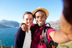 Smiling young couple on vacation taking selfie. Portrait of smiling young couple on vacation taking selfie with mobile phone Stock Photo