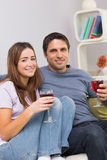 Smiling young couple with wine glasses sitting at home Royalty Free Stock Images