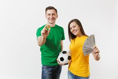 Smiling young couple, woman man, football fans in yellow green t-shirt cheer up support team with soccer ball bitcoin royalty free stock images