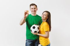 Smiling young couple, woman man, football fans in yellow green t-shirt cheer up support team with soccer ball bitcoin stock photography