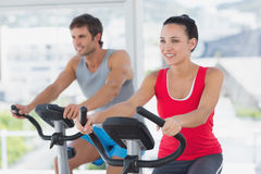 Smiling young couple working out at spinning class. In a bright gym Royalty Free Stock Photos
