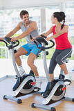 Smiling young couple working out at spinning class Stock Photography