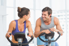 Smiling young couple working out at spinning class Royalty Free Stock Image