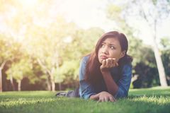 Charming smiling young hipster woman lying on green grass. Smiling young cute girl lying on green grass Are you thinking of something? Something to think about royalty free stock photos