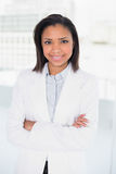 Smiling young dark haired businesswoman posing with arms crossed Royalty Free Stock Image