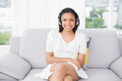 Smiling young dark haired woman in white clothes listening to music Royalty Free Stock Photo