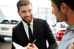 Smiling young dealer selling new car to a male customer. And filling documents Stock Photo