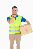 Smiling young delivery man Stock Image