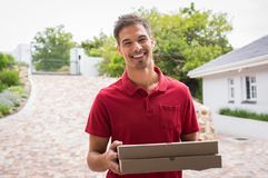 Smiling delivery boy with pizza royalty free stock photos
