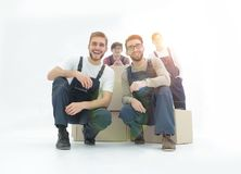 Smiling young delivery men holding stack of boxes. Isolated on w Royalty Free Stock Photos