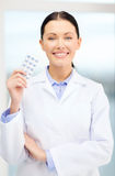 Smiling young doctor in cabinet with pills Royalty Free Stock Photography