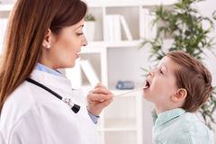 Smiling young doctor examining throat to child patient Stock Photography