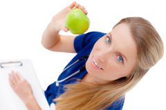 Smiling young doctor giving an green apple. Royalty Free Stock Images