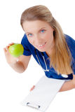 Smiling young  doctor giving an green apple. Royalty Free Stock Photography