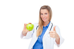 Smiling young doctor giving an green apple. Stock Images
