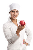 Smiling young doctor holding an apple Royalty Free Stock Photos