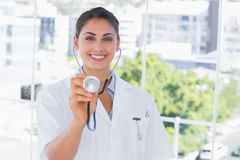 Smiling young doctor holding up stethoscope Royalty Free Stock Photo