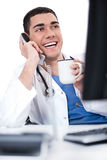 Smiling young doctor over phone Stock Images