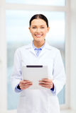 Smiling young doctor with tablet pc in cabinet Stock Photography