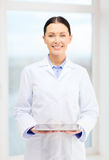 Smiling young doctor with tablet pc in cabinet Stock Image