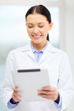 Smiling young doctor with tablet pc in cabinet Royalty Free Stock Images
