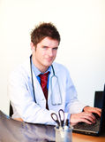 Smiling young doctor working on a computer Royalty Free Stock Photos