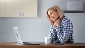 Smiling young domestic woman using laptop pc at home kitchen enjoying weekend medium close-up. Enthusiastic female housewife looking at screen of notebook stock footage
