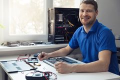 Smiling young electronics technician at work. In office Stock Photos