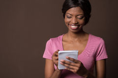 Smiling young elegant woman looking away. Beautiful happy black woman making notes Stock Photography