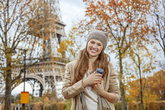 Smiling young elegant woman near Eiffel tower with cellphone Stock Photos
