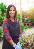 Smiling young employee in a flower nursery Royalty Free Stock Images