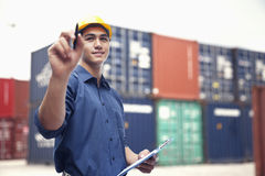 Smiling young engineer in protective work wear in a shipping yard examining cargo Stock Photo