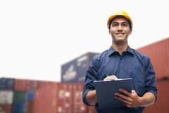 Smiling young engineer in protective work wear in a shipping yard examining cargo royalty free stock photos