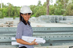 Smiling young engineer woman with rolled drawings Stock Photography