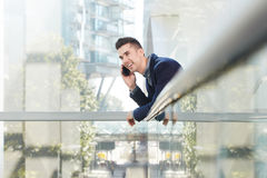 Smiling young entrepreneur standing on phone call. Portrait of smiling young entrepreneur standing on phone call Royalty Free Stock Images