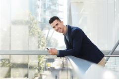 Smiling young entrepreneur standing with smart phone Royalty Free Stock Photography
